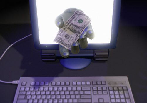 Hand Holding Money in a Computer Monitor